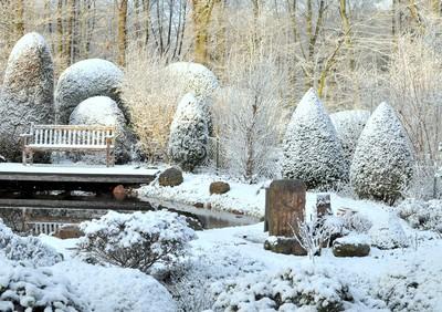 Gartenteich ruht unter einem Schneekleid